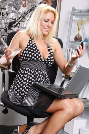 american sexy: Sexy blond at her office with her laptop, cellphone and martini Stock Photo