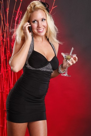 Cute blond in cocktail dress makes a call while having a martini photo