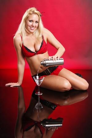 martini shaker: Cute blond in red bikini serves a martini on red Stock Photo