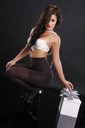 legs open: Cute brunette in pantyhose and gift box
