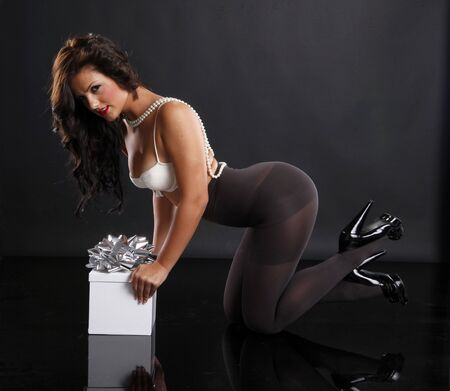 Cute brunette in pantyhose and gift box