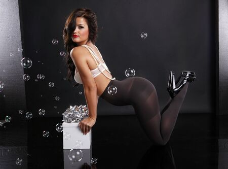 Girl in pantyhose with gift box and bubbles photo
