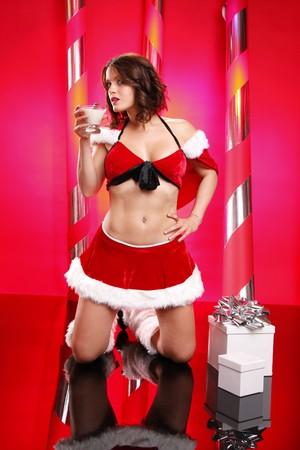 egg nog: Sexy santa enjoys an egg nog