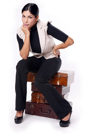 Young brunette sitting on vintage a pile of briefcases photo