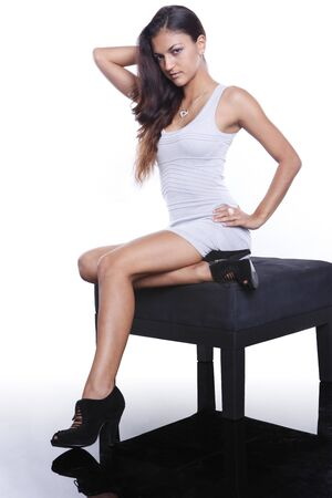 Young brunette on a black ottoman photo