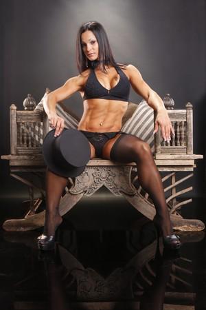 Bodybuilder master of ceremonies on vintage chair photo