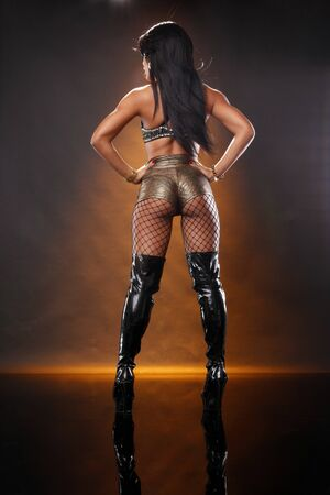 Cute brunette back in gold shorts and black tall boots