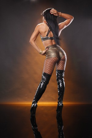 Sexy Morena en oro de pantalón y botas negras de alto  Foto de archivo - 8191248