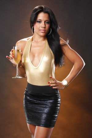 Cute brunette in black skirt and gold leotard holding wine flute