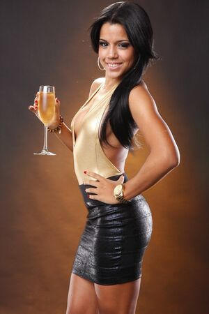 Cute brunette in black skirt and gold leotard holding wine flute photo