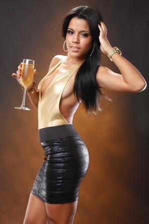 Cute brunette in black skirt and gold leotard holding wine flute photo
