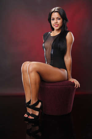 Cute brunette sitting on ottoman in black leotard on maroon Stock Photo - 8191240