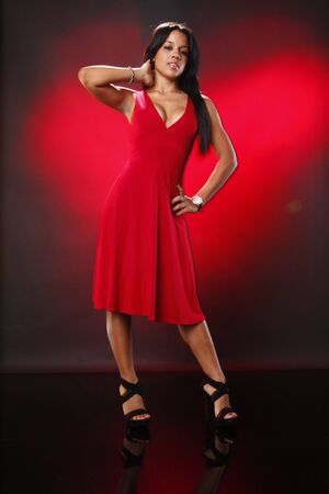 Cute brunette in red on a heart shaped beam photo