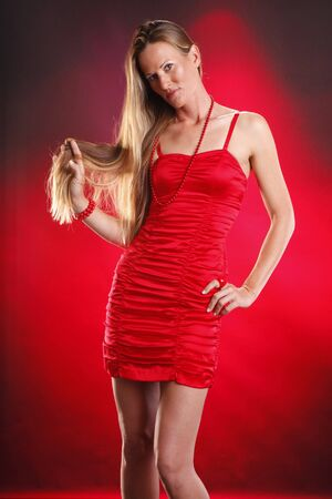Blond woman in red on red background photo