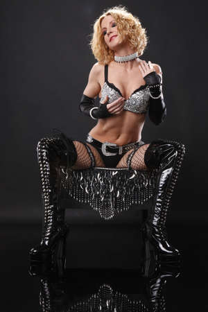 Cute brunette in high boots poses on a black ottoman photo