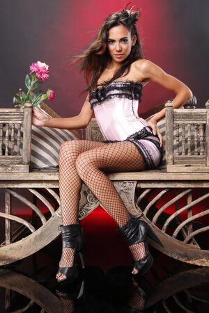 Cute brunette in pink corset on a vintage chair photo