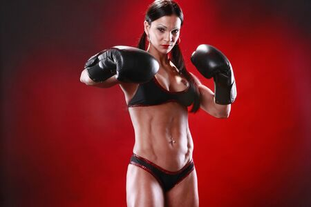 tough: Fit female boxer swings a punch