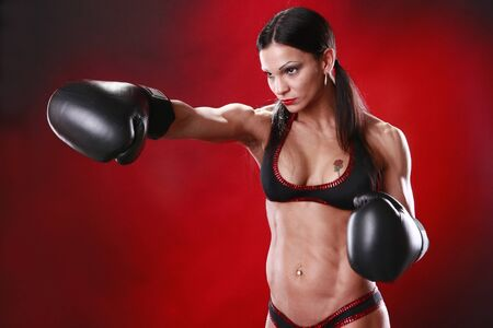 toned: Fit female boxer swings a punch