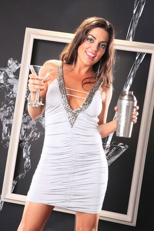 Cute brunette pours a martini with a splash outside of the frame photo