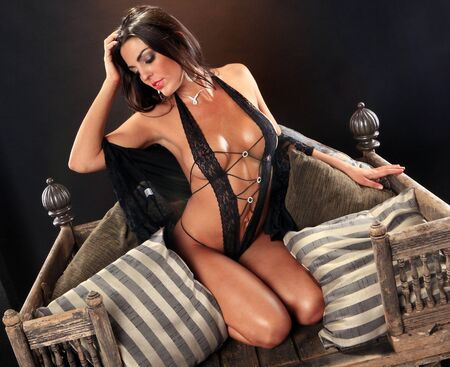 Sexy brunette on a vintage asian chair photo
