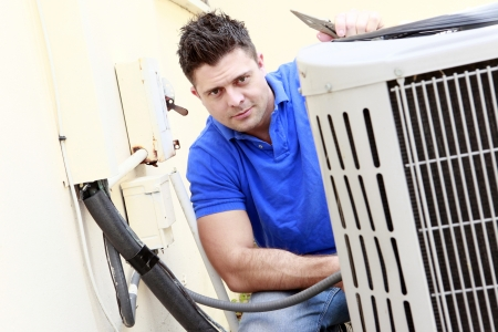 home repair: Technician inspects an AC unit