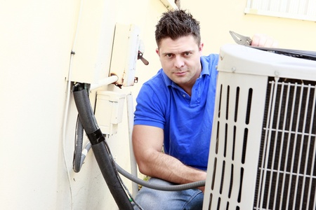 compressore: Technician inspects an AC unit