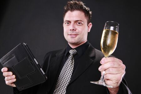 Businessman cheers with his tablet pad in one hand photo