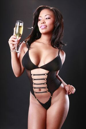 jamaican: Cute African-American in black swimsuit holds a sparkling flute