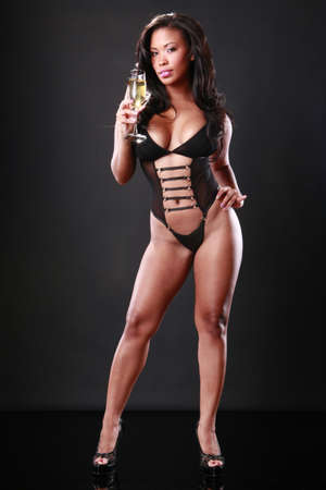 sexy african american woman: Cute African-American in black swimsuit holds a sparkling flute