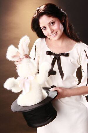 Cute magician pull a bunny out of a top hat photo