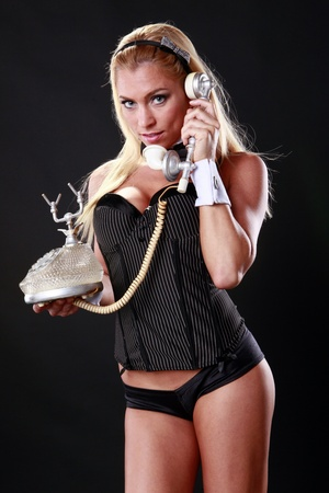 Gorgeous caucasian picks a call on a vintage phone