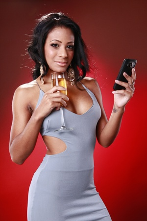 Cute caribbean girl texting about her drink photo