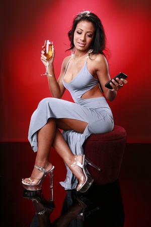 Cute caribbean girl texting about her drink Stock Photo - 9572627