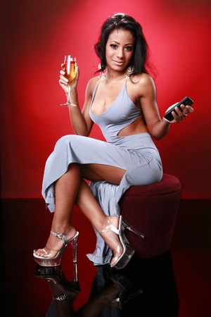 Cute caribbean girl texting about her drink Standard-Bild