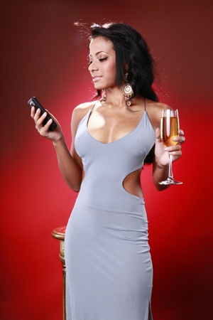 lounge: Cute caribbean girl texting about her drink Stock Photo