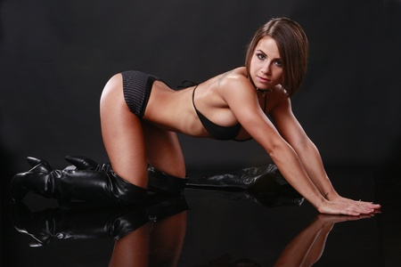 leather background: Fit brunette in black bikini and leather jacket