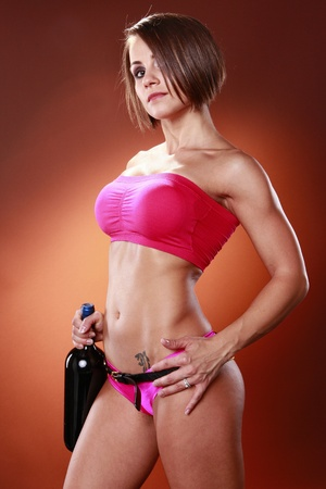 amber light: Fit woman and large wine bottle Stock Photo