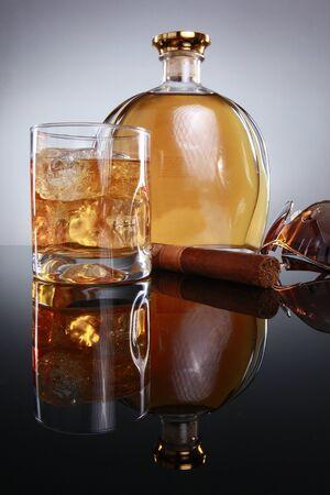 Hard liquor on the rocks, havana cigar, and designer shades Imagens