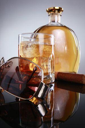 moonshine: Hard liquor on the rocks, havana cigar, and designer shades Stock Photo