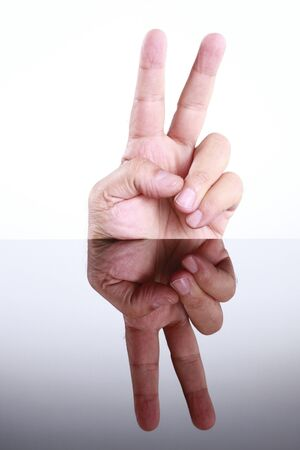 Hand does the victory sign and mirror image photo