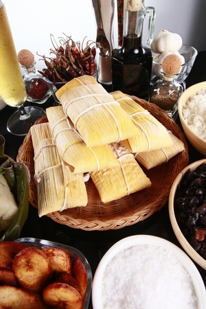 Staple latino sides, tamale, rice, plantains, and black beans photo