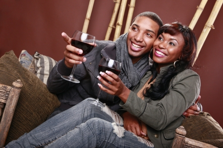 Young couple enjoys red wine at the bamboo foyer Stock Photo - 11056745