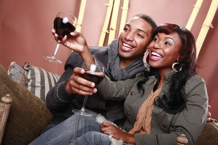 african american vintage: Young couple enjoys red wine at the bamboo foyer
