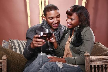 couple afro americain: Jeune couple b�n�ficie de vin rouge au foyer de bambou