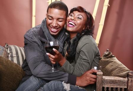 Jong paar geniet van rode wijn bij de bamboe foyer Stockfoto