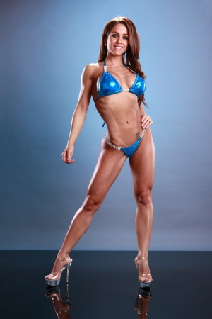 body built: Fitness poses on blue Stock Photo