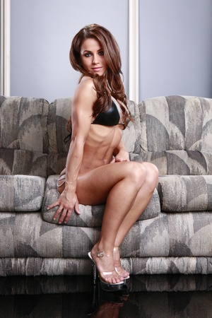 Fit young woman sitting on a couch photo