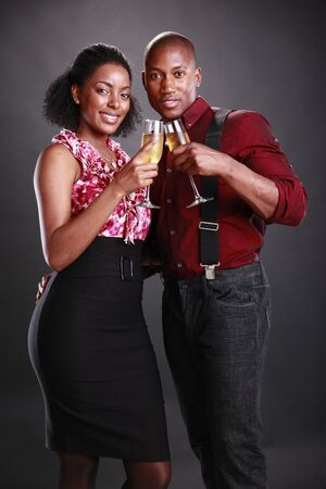An african american couple cheers with champagne flutes photo