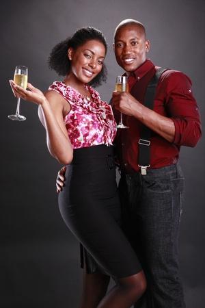 Un par de gritos africanos americanos con copas de champán Foto de archivo - 11553094