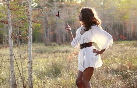 transparent dress: Sexy African American plays with a butterfly in the woods Stock Photo